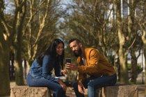 Pareja romántica usando teléfono móvil en la ciudad - foto de stock