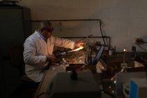 Lavoratore maschio che utilizza la torcia di saldatura in fabbrica di vetro — Foto stock