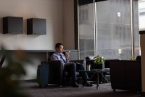 Businessman talking on mobile phone in lobby at hotel — Stock Photo