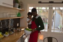 Father cooking food while holding his son in kitchen at home — Stock Photo