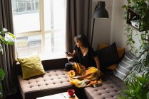 Mujer usando teléfono móvil en el sofá en la sala de estar en casa - foto de stock
