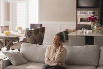 Femme âgée parlant sur téléphone portable dans le salon à la maison — Photo de stock
