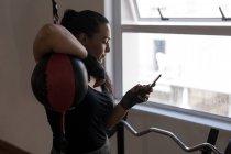 Giovane pugile femminile che utilizza il telefono cellulare in palestra — Foto stock