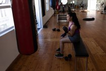 Side view of female boxer exercising with dumbbell in fitness studio — Stock Photo