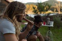 Young man eating sausage at campsite — Stock Photo