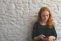 Donna rossa che utilizza il telefono cellulare in caffè — Foto stock
