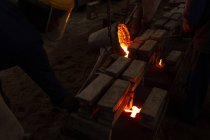 Trabajadores vertiendo metal fundido de frascos en moldes en fundición - foto de stock