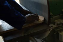 Close-up of worker using sharpening machine in foundry workshop — Stock Photo