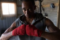 Portrait of male boxer standing with fests in boxing club — Stock Photo
