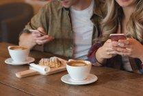Крупный план пары с использованием мобильного телефона в кафе — стоковое фото