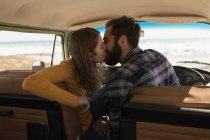 Romantic couple kissing in vehicle on road trip — Stock Photo