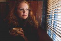 Mulher ruiva cuidadosa olhando pela janela cega no café — Fotografia de Stock