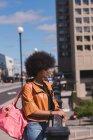 Femme réfléchie debout par rambarde dans la ville — Photo de stock