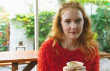 Donna rossa che tiene una tazza di caffè in un caffè all'aperto — Foto stock