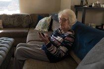 Пожилая женщина пользуется мобильным телефоном на диване в гостиной дома — стоковое фото