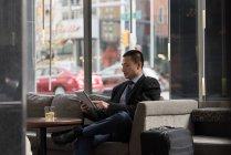 Businessman using digital tablet on sofa in hotel — Stock Photo
