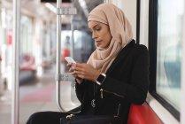 Хиджаб-женщина, с помощью мобильного телефона во время поездки в поезде — стоковое фото