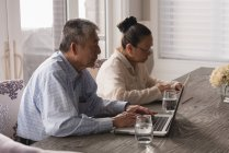 Senior couple using laptop and digital tablet on dining table at home — Stock Photo