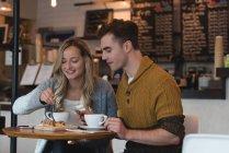 Jeune couple ayant des aliments sucrés au café — Photo de stock