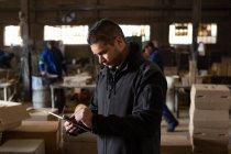 Uomo attento utilizzando tablet digitale in fonderia — Foto stock
