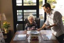 Hijo prepararse para servir la comida a la madre sobre la mesa en casa - foto de stock