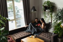 Пара с супом на диване в гостиной дома — стоковое фото