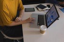 Partie médiane de l'exécutif féminin utilisant un ordinateur portable dans la salle de conférence — Photo de stock