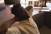 Мужчина исполнительный расслабляющий с руками за головой в кафетерии в офисе — стоковое фото