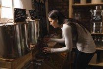 Belle femme remplissant le condiment en pot au supermarché — Photo de stock