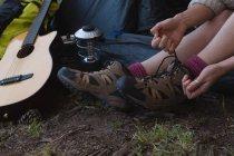 Primo piano della donna che indossa le scarpe al campeggio — Foto stock