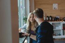 Casal interagindo enquanto toma café no café — Fotografia de Stock