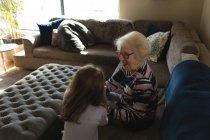 Бабушка и внучка взаимодействуют друг с другом на диване в гостиной дома — стоковое фото