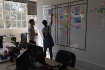 Executivos discutindo sobre notas pegajosas no escritório — Fotografia de Stock