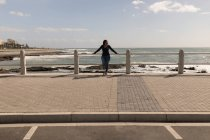 Disabled woman standing on promenade near sea — Stock Photo
