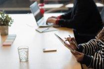 Средняя секция женщин-руководителей с помощью цифрового планшета в офисе — стоковое фото