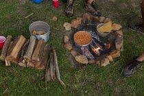 Comida que se prepara en la hoguera en el campamento - foto de stock