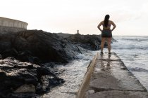 Rear view of female jogger standing at promenade near sea side — Stock Photo
