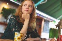 Продуманий руда жінка відпочити в кафе — стокове фото