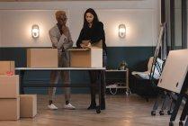 Empresária unboxing caixa de papelão no escritório — Fotografia de Stock