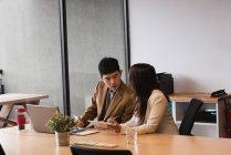 Руководители обсуждают за цифровым планшетом в офисе — стоковое фото