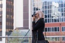 Hijab woman clicking photo in digital camera at balcony — Stock Photo