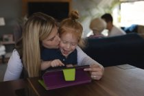 Mother kissing her daughter while using digital tablet in living room at home — Stock Photo