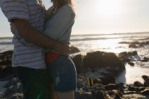 Mid section of couple embracing on the beach — Stock Photo