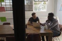 Руководители обсуждают за ноутбуком в конференц-зале в офисе — стоковое фото
