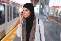 Femme hijab parlant sur le téléphone portable dans la plate-forme à la gare — Photo de stock