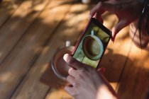 Close-up of woman taking picture of coffee cup in cafe — Stock Photo