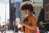 Mulher usando telefone celular ao ter comida na cidade — Fotografia de Stock