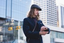 Man checking time on watch while walking on the street in the city — Stock Photo