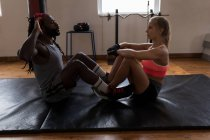 Female trainer assisting male boxer in doing crunches in fitness studio — Stock Photo