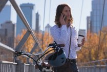 Uomo che parla al cellulare mentre prende un caffè sul ponte in città — Foto stock